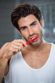 Молодой человек чистит зубы