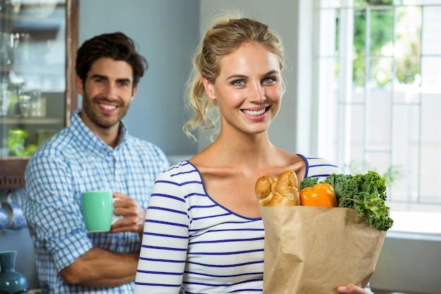 台所でコーヒーカップを持つ男ながら食料品の袋を運ぶ女性