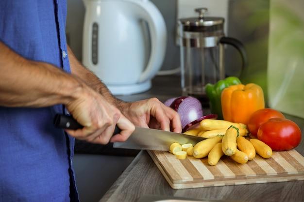 キッチンカウンターで野菜を刻んで男