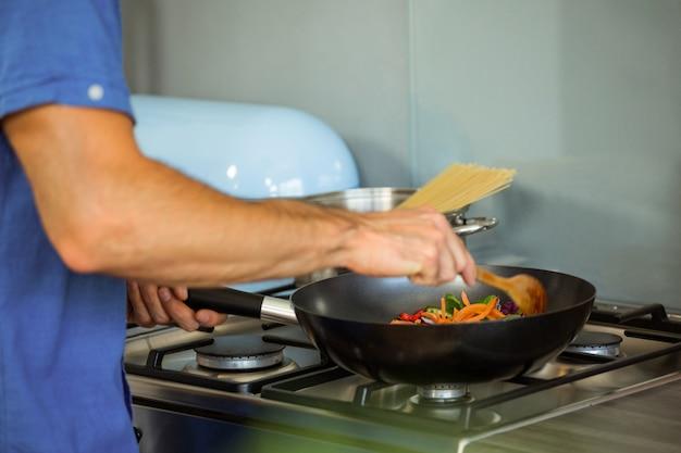 Мужчина готовит еду на кухне