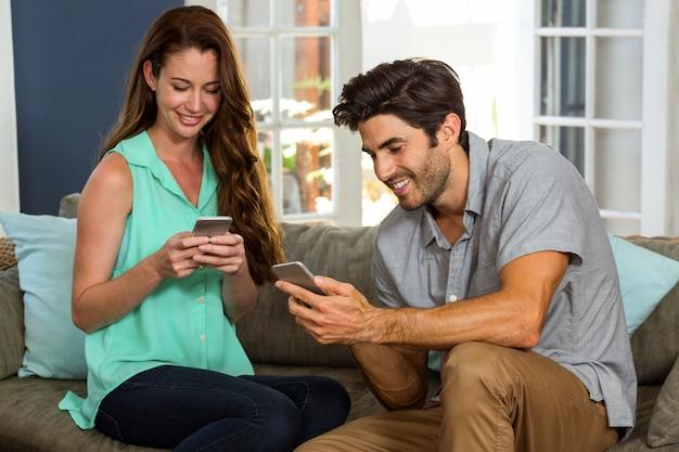 携帯電話を見て、笑顔のカップル