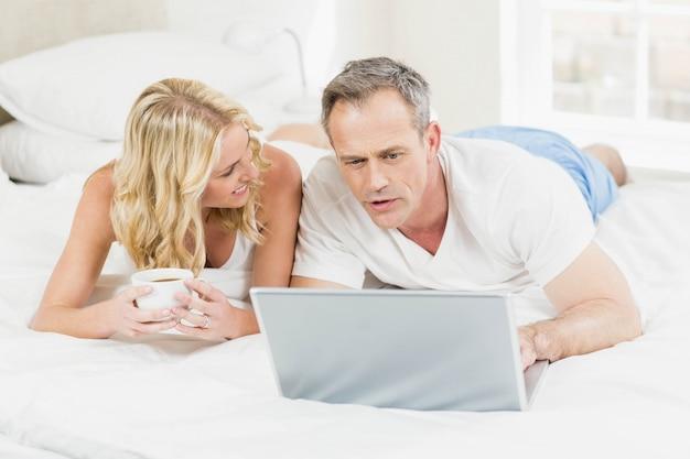 かわいいカップルが彼らの寝室のベッドでノートパソコンを使用して