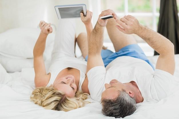 タブレットとスマートフォンを使用してベッドの中でかわいいカップル