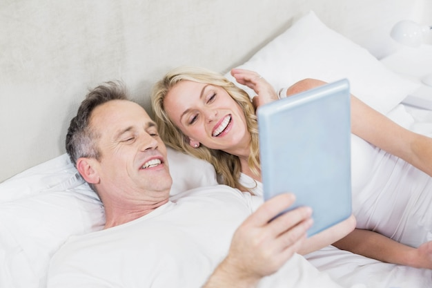 かわいいカップルのベッドでタブレットを使用して