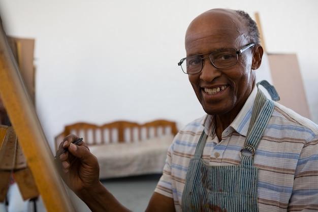 イーゼルに描く笑顔の年配の男性の肖像画を間近します。