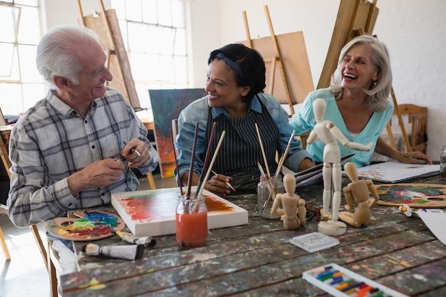 テーブルで陽気なシニア男性と女性アーティスト
