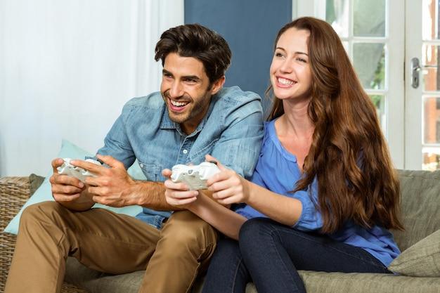 Молодая пара играет в видеоигры, сидя на диване