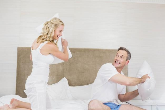 枕をしているかわいいカップルがベッドの中で戦う