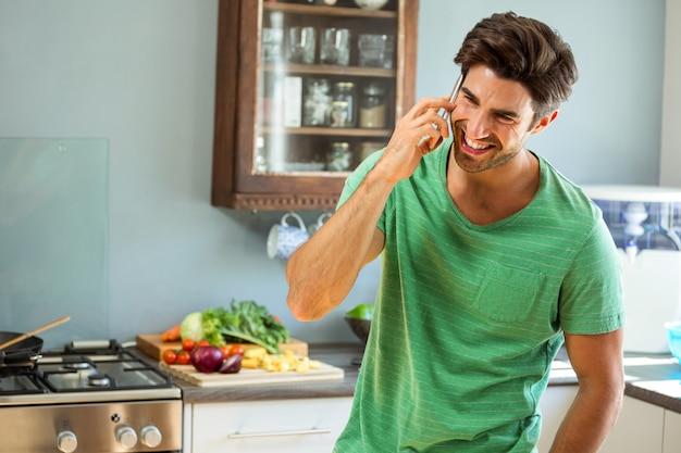 Счастливый человек разговаривает по телефону на кухне