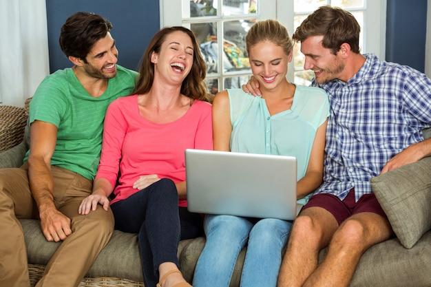 Счастливые друзья сидят на диване и с помощью ноутбука
