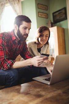 Пара покупок в интернете на ноутбуке в гостиной