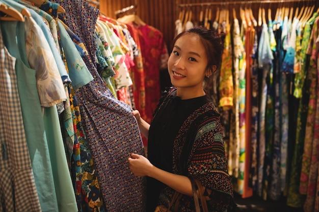 Портрет улыбающейся женщины, выбирающей одежду