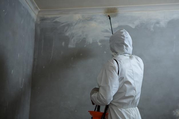 壁に害虫駆除を行う男