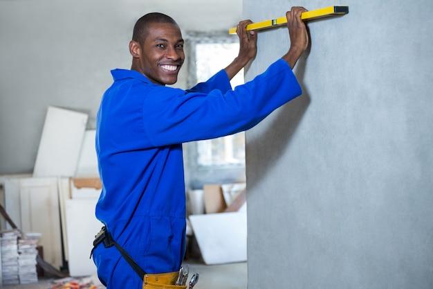 Счастливый мастер измеряет стену с уровнем духа