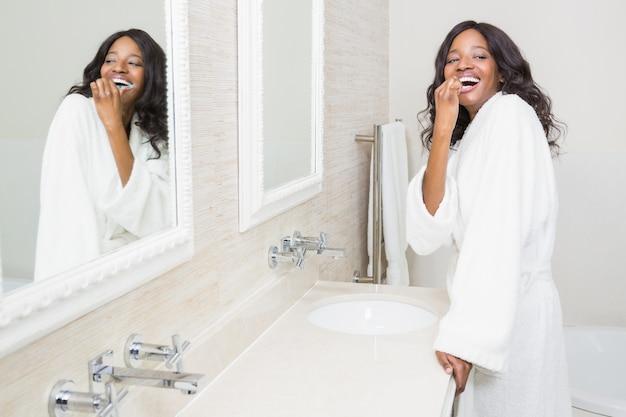 Молодая женщина чистит зубы