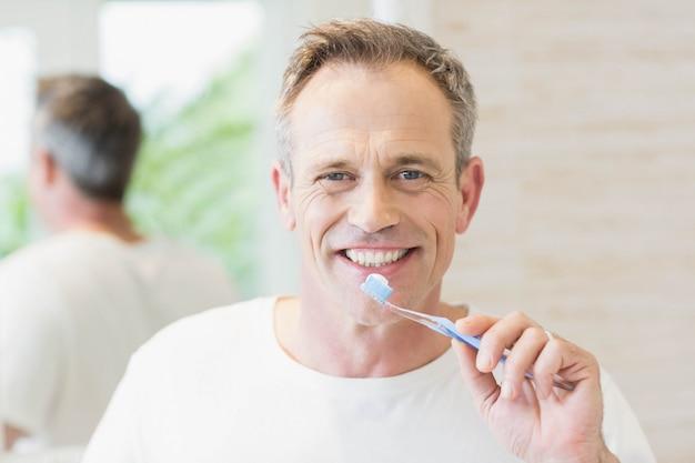 ハンサムな男がトイレで彼の歯を磨く