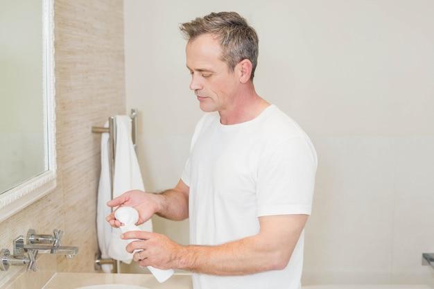 Красивый мужчина, применяя крем в ванной комнате