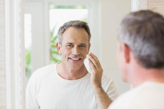 Красивый мужчина, применяя пены для бритья в ванной комнате