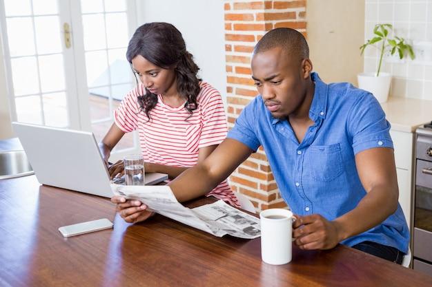 台所でラップトップを使用して若い女性