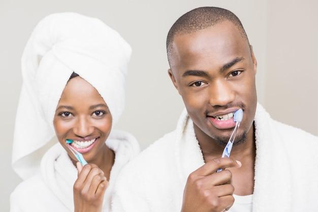 Молодая пара чистит зубы