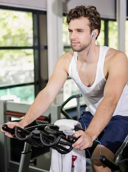 Человек слушает музыку во время тренировки на велотренажере