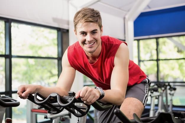 Человек работает на велотренажере в спиннинг класса