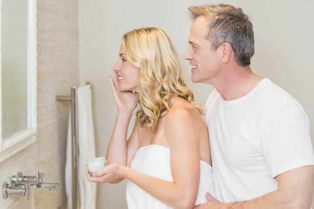 女性の後ろに夫と一緒に浴室でクリームを適用します。