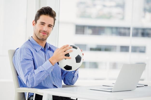 Бизнесмен держит футбольный мяч