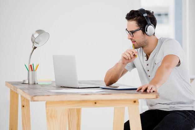 彼の机で働く若い男