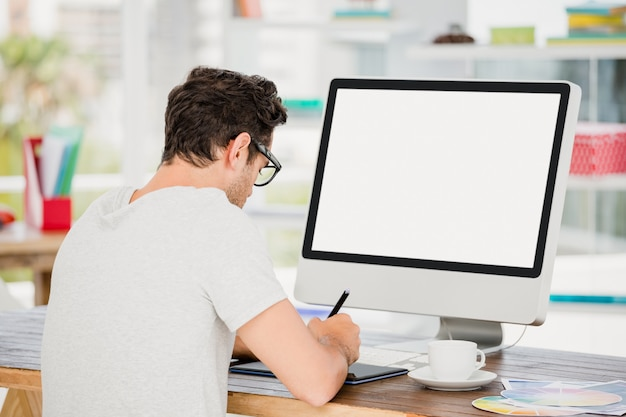 Молодой человек с помощью планшета и компьютера
