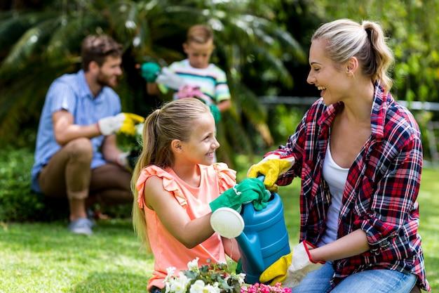 Счастливая мать и дочь поливают цветы во дворе