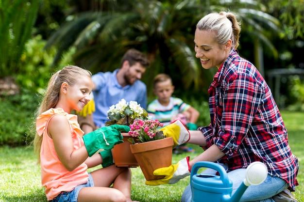 Мать и дочь с цветочными горшками, сидя во дворе