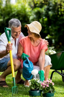 Пожилая пара с садовой техникой на дворе
