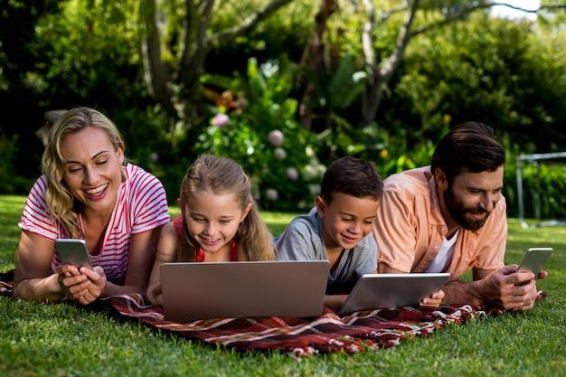 庭に横たわっている間、技術を使用する家族