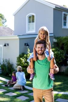 Улыбающийся отец несет дочь на плечах во дворе