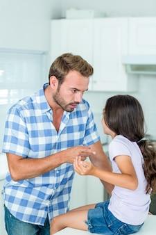 Отец, указывая во время разговора с дочерью на кухне