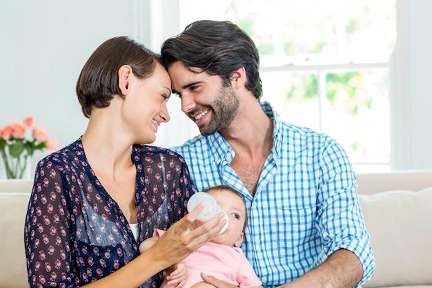 息子にミルクを与えながら笑顔の親