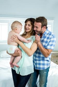 Веселые родители с милым сыном у кровати