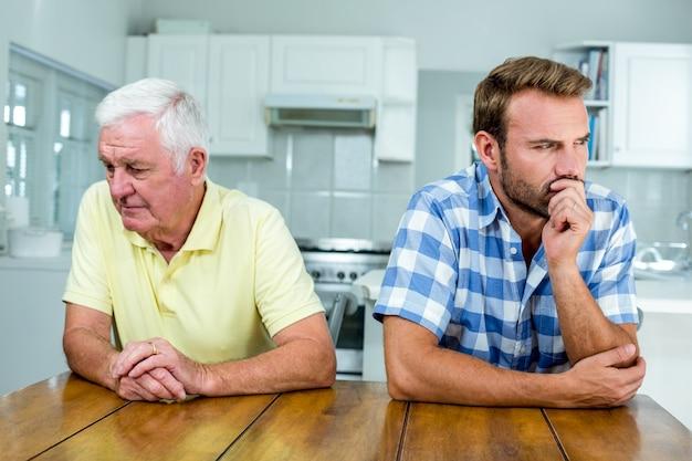 緊張した父と息子が台所のテーブルに座って