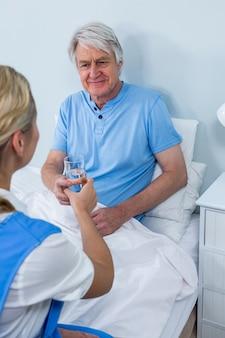 年配の男性が自宅で薬を与える看護師