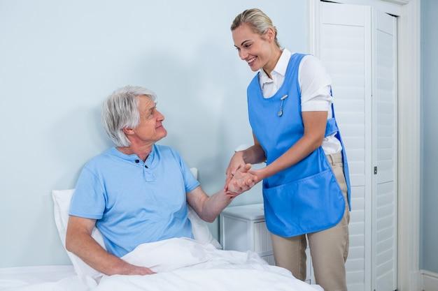 看護師が病院で年配の男性の手を握って