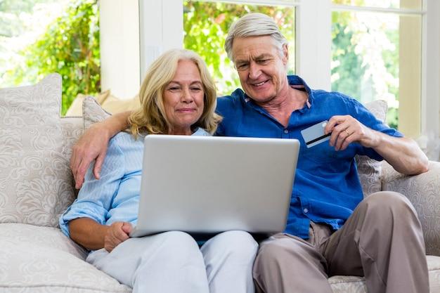 自宅のソファーに座りながらラップトップを使用して年配のカップル