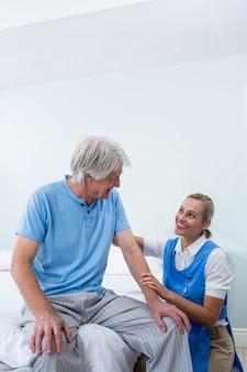 病院で年配の男性を慰める笑顔の看護師