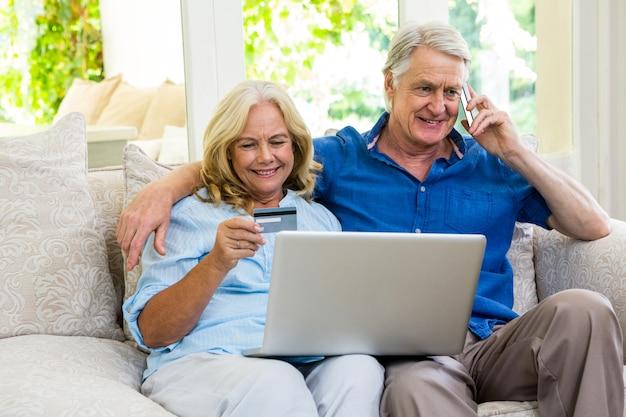 自宅の電話で話しながらラップトップを使用して年配のカップル