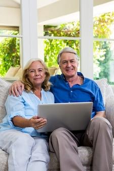自宅でラップトップを保持している年配のカップルの肖像画
