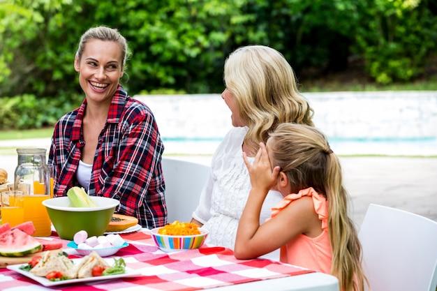 Улыбается женщина, принимая к матери и дочери за столом