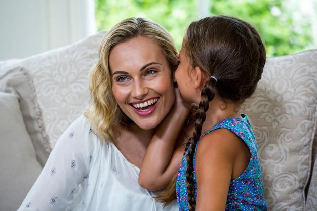 Девушка шепчет на ухо улыбающейся матери