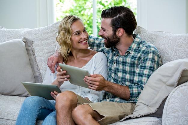 デジタルタブレットを保持しながらお互いを見ているカップル
