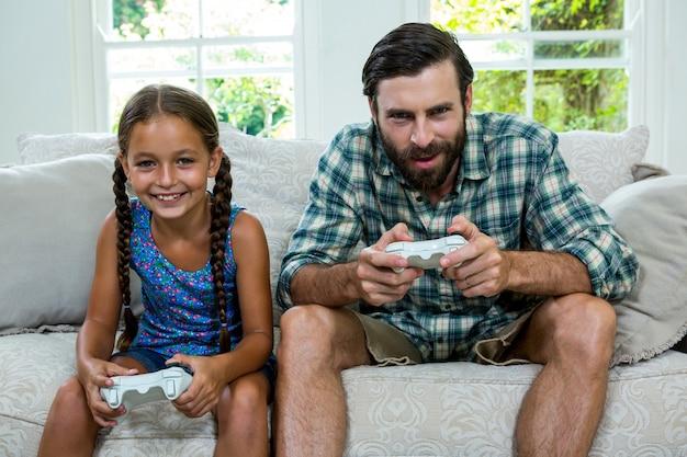 父と娘が自宅でビデオゲームをプレイの肖像画