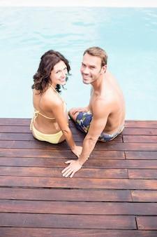 笑顔とプールサイドで座っている若いカップルの肖像画